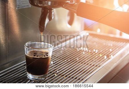 Cup of espresso with coffee machine. Brewing coffee at cafe.