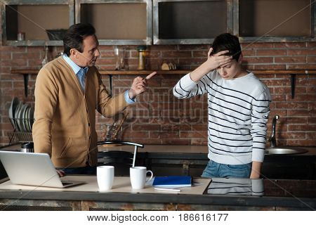 Be attentive next time. Strict man raising his forefinger upwards and leaning right hand on the table while standing in opposite his son