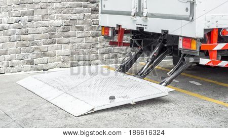 Delivery truck and transportation car concept - Close up hydraulic tray of delivery truck parking for delivery a parcel to receiver and copyspace