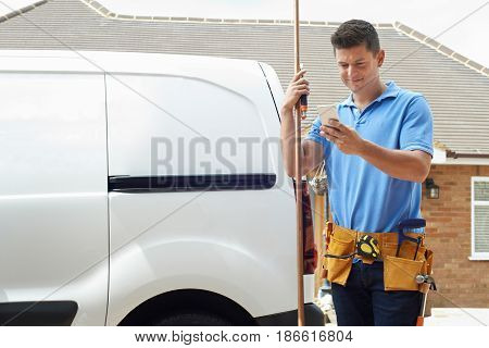 Plumber With Van Using Mobile Phone Outside House