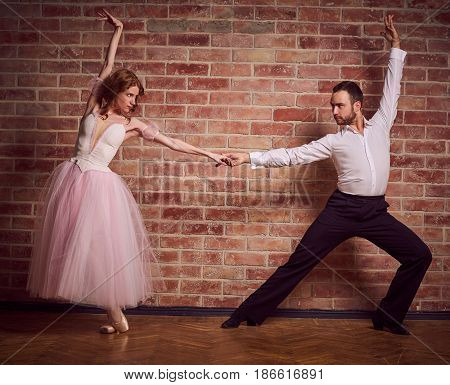 Female ballet dancer in pink dress and pointe learning latin dance with male partner