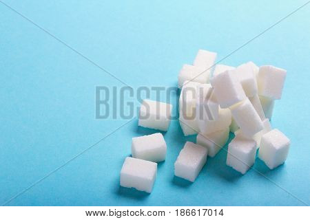 Sugar cubes scattered on a blue background with an empty space for text copy paste