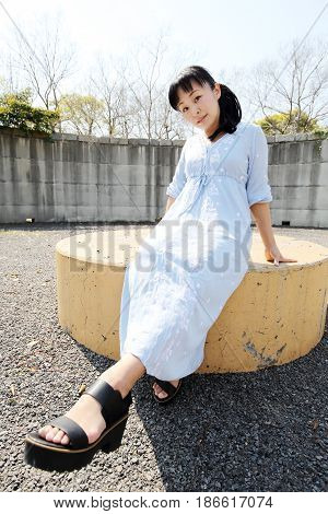 Portrait of young japanese woman sitting on a bench