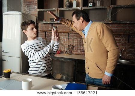 Made to hit him. Attentive boy raising his arms while protecting himself and looking at his dad