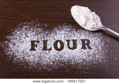 The word flour is written on the table. Flour is scattered on brown discs and a spoon lies next to it