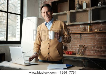 Feeling happiness. Smiling male person holding cup with tea in left hand touching computer while looking straight at camera