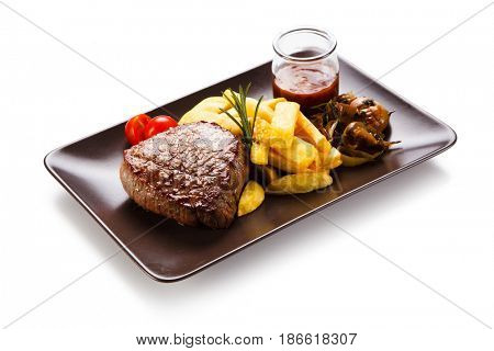 Grilled beefsteak with french fries and mushrooms on white background