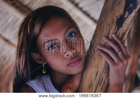 Portrait of a beautiful native Asian girl climbing on the sunshade umbrella