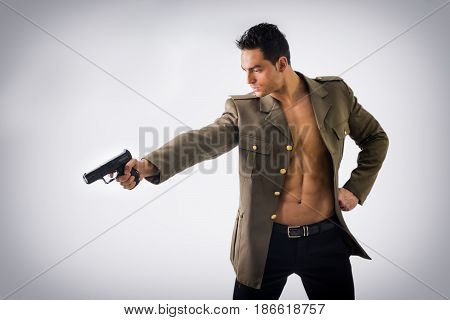 Portrait of an Athletic Handsome Man in an Open Military Jacket Pointing a Gun While looking to the Left of the Frame, on Light Background.