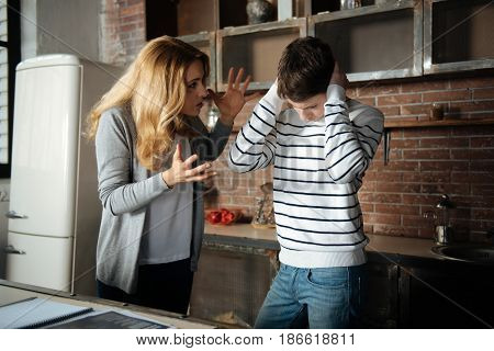 I want to punish you. Nervous young woman raising her hands standing in semi position while going to punish her son poster