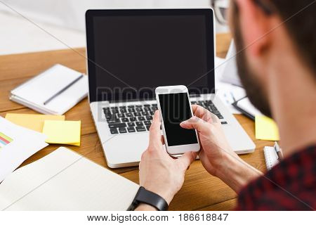 Businessman with mobile and laptop at workplace, copy space on screen. Man in casual with digital devices, over shoulder view