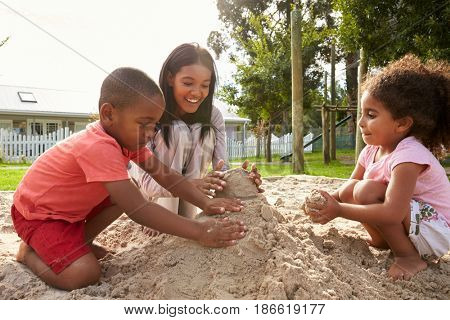 Teacher At Montessori School Playing With Children In Sand Pit