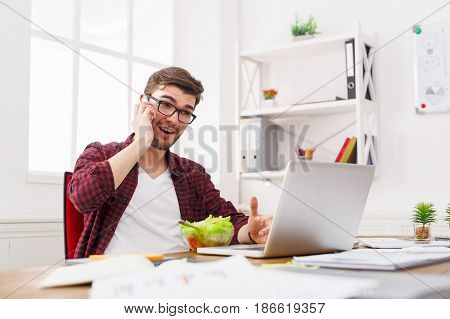 Busy at work. Man has business lunch in office, talking on mobile and reading papers. Overworking concept.