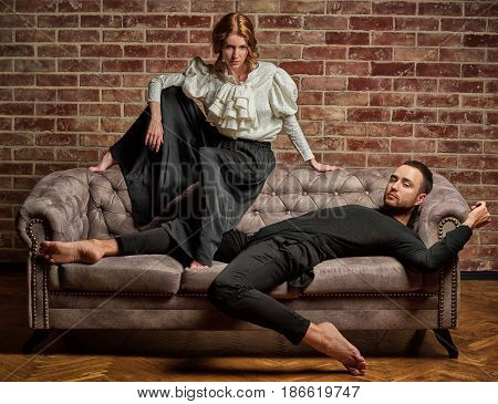 Female ballet dancer and male latin dancer in contemporary style in pose lie on the sofa