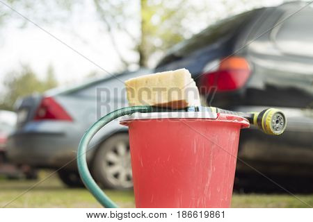 Pail, sponge and garden hose on the background of cars.