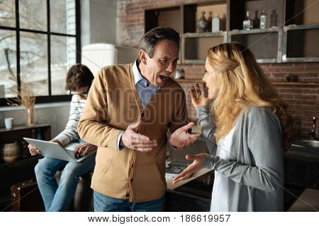Family quarrel. Delighted blonde female standing opposite her husband and talking to him while actively gesticulating