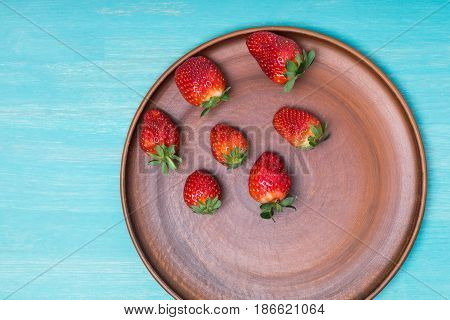 Fresh Red Strawberries On Ceramic Plate On Blue Wooden Tabletop, Berries Top View Concept