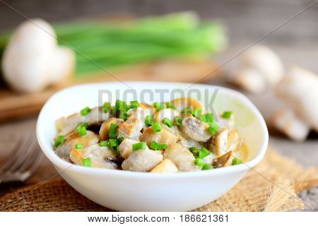 Roasted mushrooms with sour cream and fresh green onions in a bowl. Vegetarian meal. Easy wholesome mushrooms recipe. Fresh mushrooms, green onions on vintage wooden table. Closeup