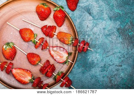 Whole Fresh Red Strawberries And Sliced Strawberries On Wooden Skewers In Ceramic Plate, Berries Top