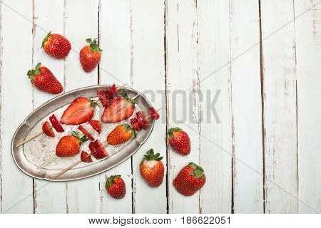 Whole Fresh Red Strawberries And Sliced Strawberries On Wooden Skewers In Vintage Plate On Wooden Ta