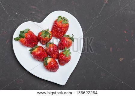 Fresh Red Strawberries On White Heart Shaped Plate On Black Tabletop, Berries Top View Concept