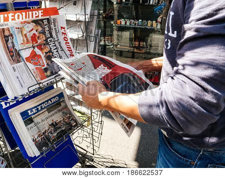 PARIS FRANCE - MAY 15 2017: Black ethnicity man buys Liberation with Good Luck to Macron text newspaper reporting handover ceremony presidential inauguration of the newly elected French President Emmanuel Macron in Paris France