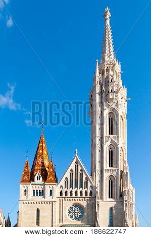 Roman Catholic Matthias Church and Holy Trinity plague column at Fisherman's Bastion in Buda Castle District, Budapest, Hungary, Europe. Sunny day shot with clear blue sky.