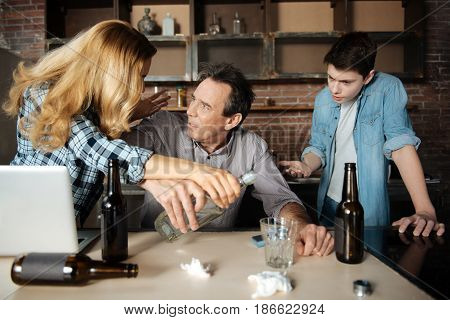I can help you. Pessimistic man holding strongly the bottle leaning on the table while looking at his wife