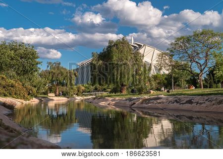 Valencia, Spain Gardens in the old dry riverbed of the Turia river, water reflection. Beautiful landscape leisure and sport area with trees, grass and water mirror
