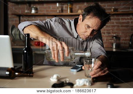 Life-saving method. Enigmatical male person looking at his glass, holding bottle in right hand