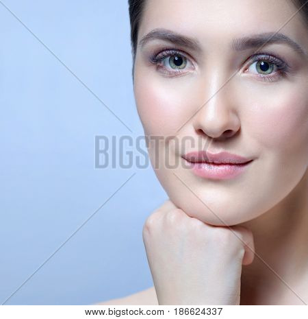 Beauty Spa Woman with Perfect skin Portrait.Young Caucasian with Fresh looking Skin.Face Closeup. Blue background. Looking at camera.