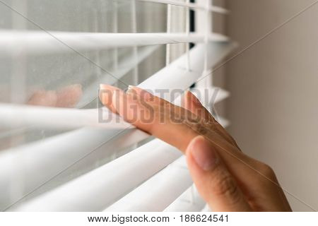 Windows jalousie. woman peeking through window blinds. Male hand separating slats of venetian blinds with a finger to see through