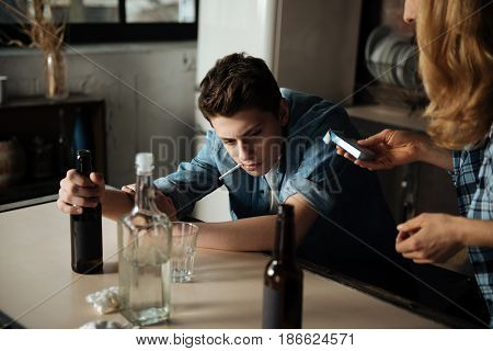 Throw it away. Resolute boy leaning elbows on table holding bottle in right hand looking sideways