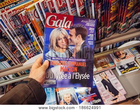 PARIS FRANCE - MAY 15 2017: Man buys Gala magazine with Emmanuel Macron and his wife Brigitte Trogneux during handover ceremony presidential inauguration of the newly elected French President Emmanuel Macron in Paris France