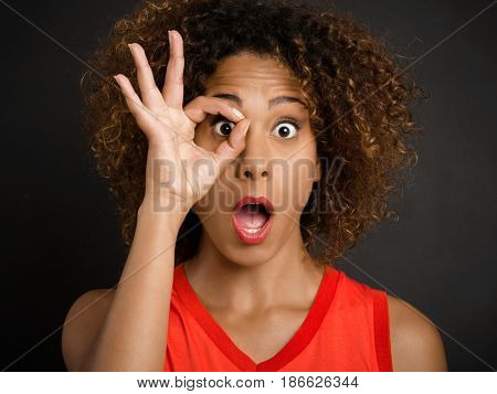 Portrait of a beautiful African American woman looking through her fingers