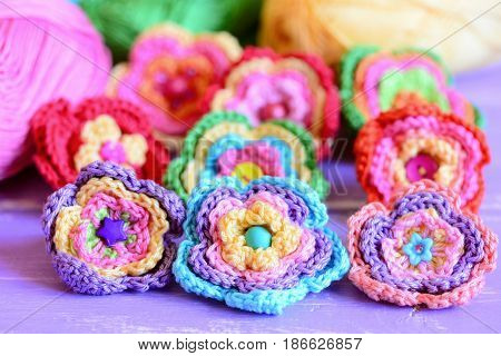 Vivid crochet flowers on purple wooden background. Crocheted flowers from colourful cotton yarn. Easy summer handmade crafts idea. Closeup