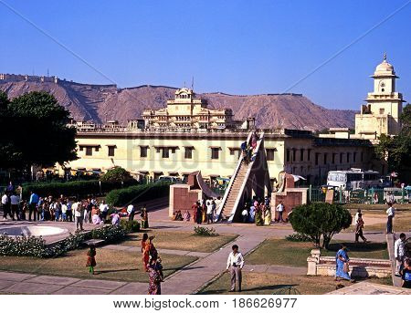 JAIPUR, INDIA - NOVEMBER 24, 1993 - Elevated view of people looking at the giant sundial known as the Samrat Yantra at Jantar Mantar Jai Singhs Observatory with the City Palace also known as the Chandra Mahal to the rear Jaipur Rajasthan India, November 2