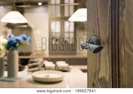 Opened wooden door to modern kitchen and plate for cooking.