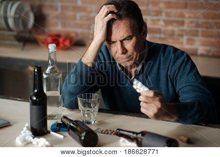 Have headache. Disappointed man in years putting right hand on head holding tablets in left one while looking at bottles