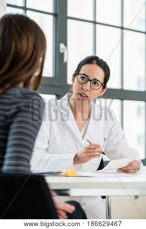 Female physician listening to her patient during consultation while sitting down in the office of a modern medical center