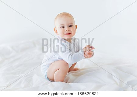 Adorable Baby Boy Sitting On Bed  Isolated On White, 1 Year Old Baby Concept