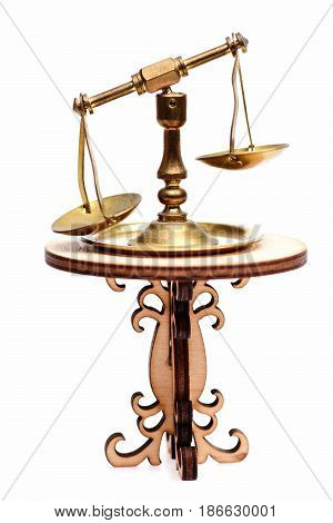 Golden scales or libra of justice on decorative table isolated on white background. Justice and equality concept