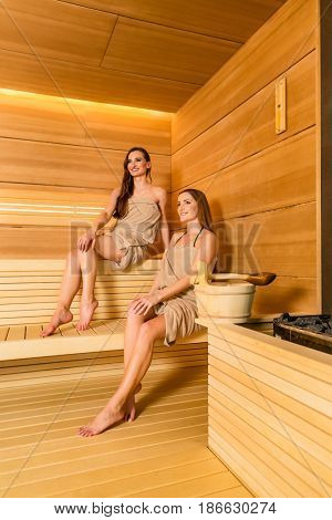 Full length of two female best friends smiling while enjoying the therapeutic effect of a dry sauna in a modern wellness center