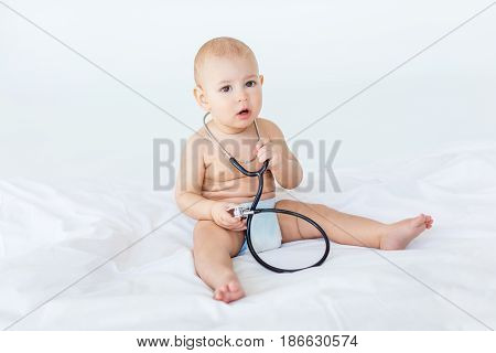 Adorable Baby Boy Sitting On White Bed With Stethoscope, 1 Year Old Baby Concept