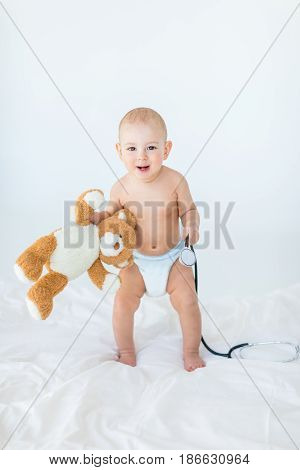 Adorable Small Baby Boy Standing On Bed And Holding Stethoscope With Teddy Bear, 1 Year Old Baby Con