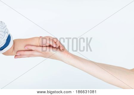 Close-up Partial View Of Mother Holding Hand Of Cute Little Child Isolated On White