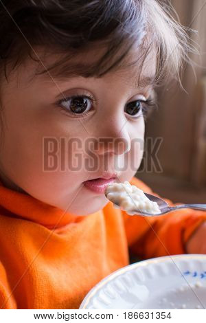 Child girl sitting at the table and feed her porridge with a spoon.