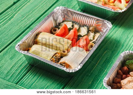 Healthy restaurant food delivery. Take away foil lunch boxes with copy space at green wood. Stuffed leek with fresh vegetables