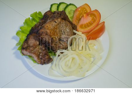 Juicy grilled meat on a white plate with onions, cucumbers and tomatoes and a salad.