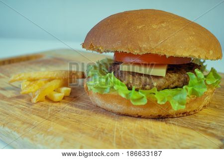 A traditional American burger with a chop, tomato and cheese on a salad leaf. French fries. fast food.